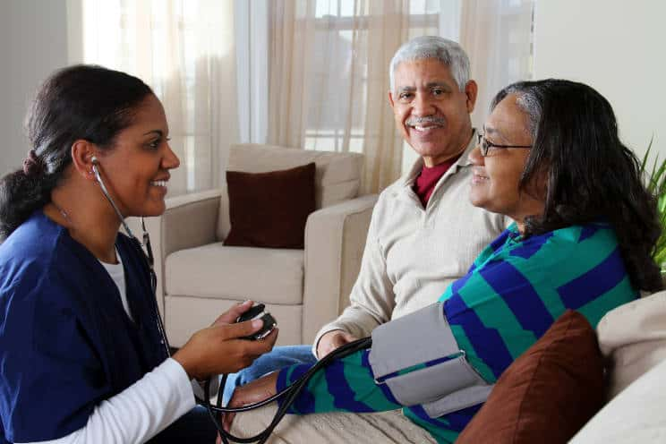 Home health care professional taking blood pressure