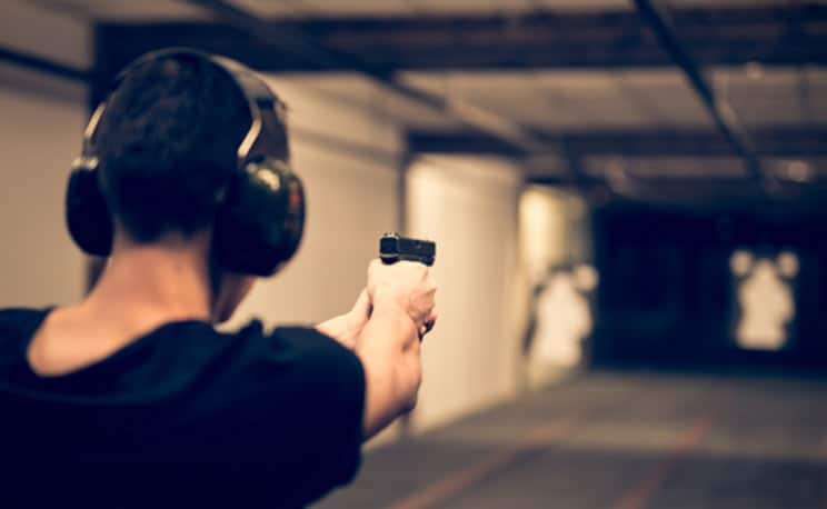 man firing a gun at firing range
