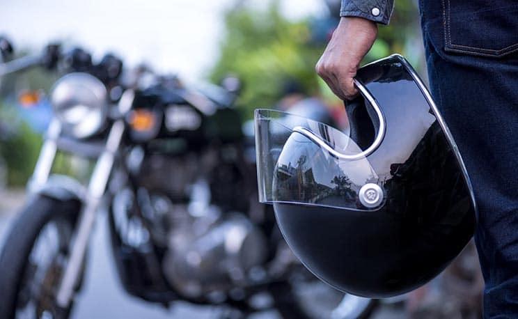 Motorcyclist holding helmet